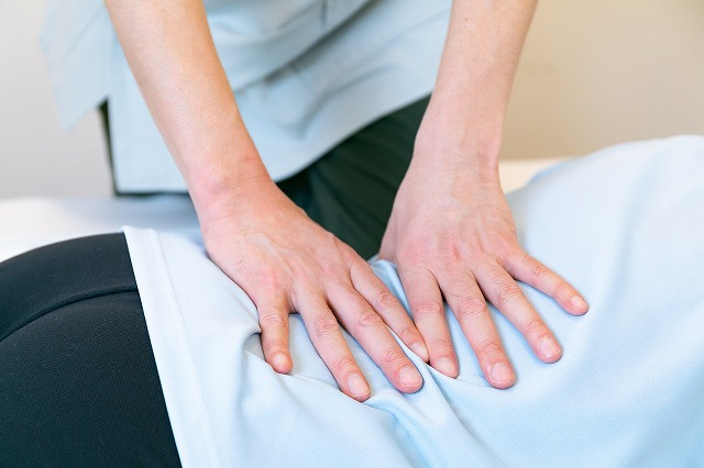 お客さんの腰のあたりにトリガーポイントセラピーによる筋肉の調整を行っている写真