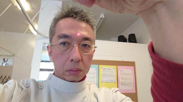 院長が自分自身で非接触型体温計を用いて検温している時の写真