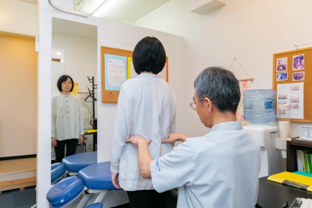 院長がお客さんの身体のゆがみを検査している画像